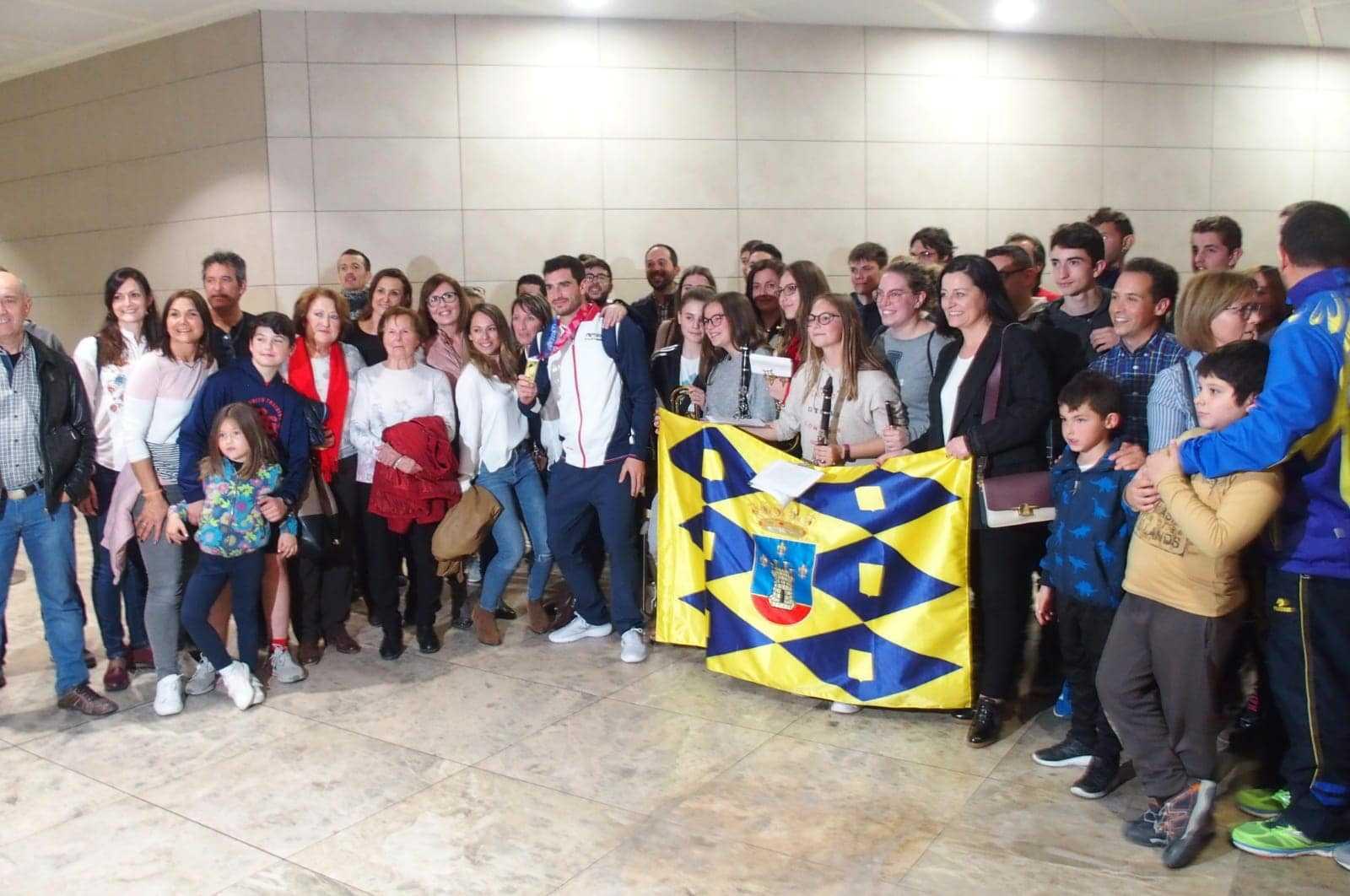 Amigos, familiares, autoridades y la banda de música de Onil reciben al atleta Jorge Ureña en el aeropuerto de Alicante